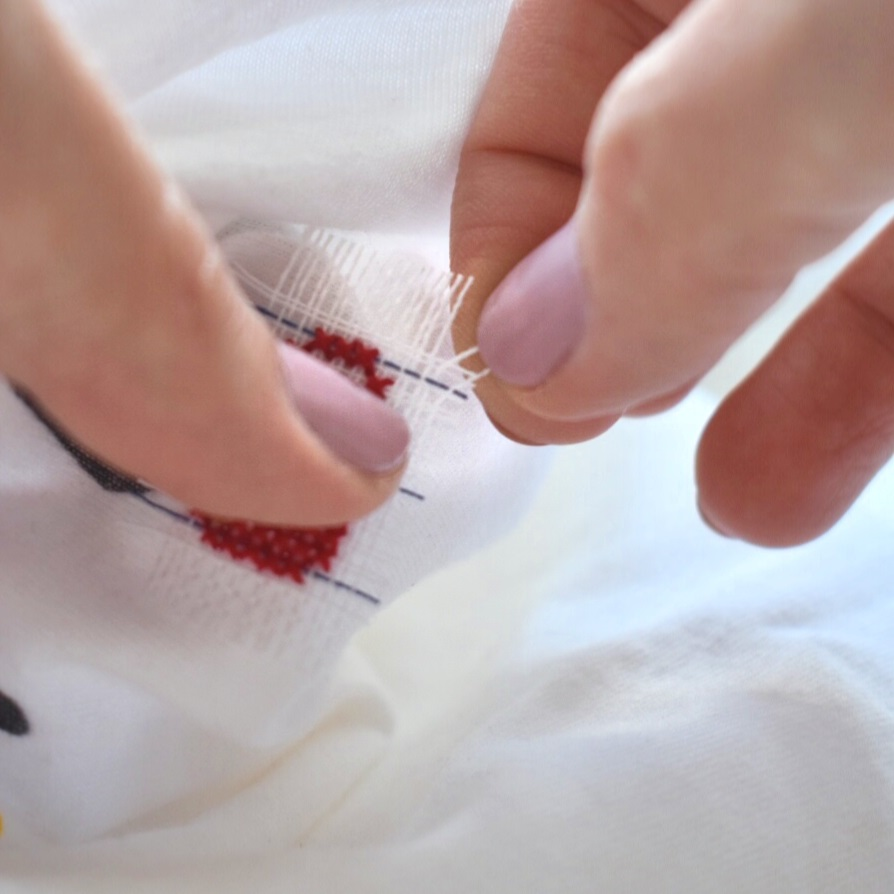 using-hands-to-pull-out-waste-canvas-threads